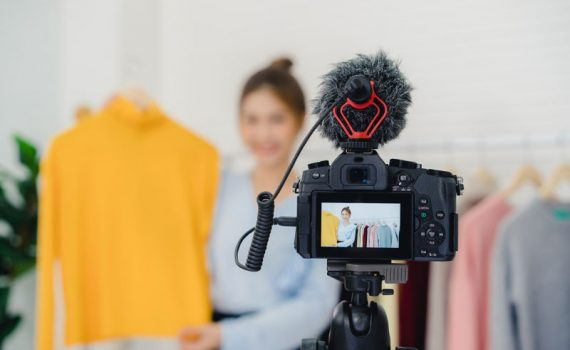 Mujer promociona producto ante cámara para hacer video marketing y así demostrar los beneficios del video marketing