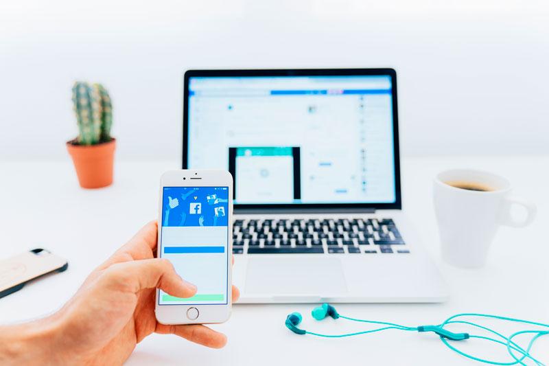 Celular y laptop con cuentas de facebook activas. La seguridad en facebook hace de tu uso de la red social algo confiable.